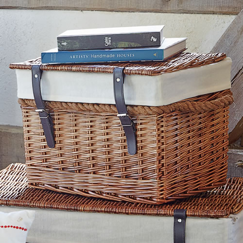Lidded wicker chest with rope handles and faux leather fastening straps