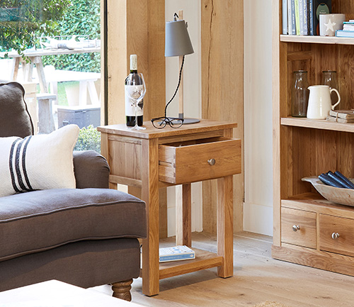 Solid oak lamp table with a storage drawer and shelf