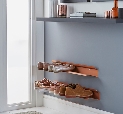Wall mounted metal shoe rack in a copper finish